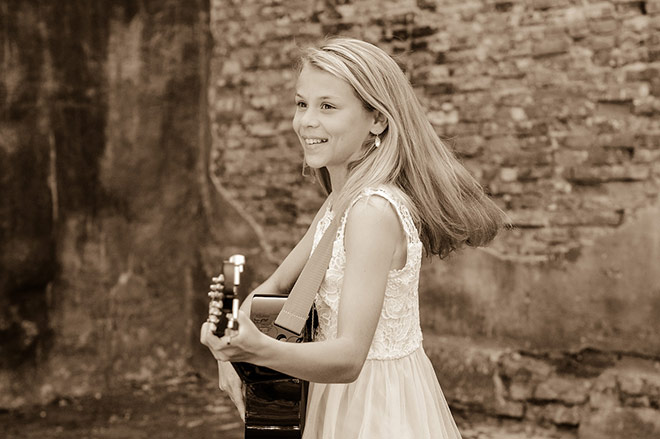 Mary Kate Ayers smiling with her guitar
