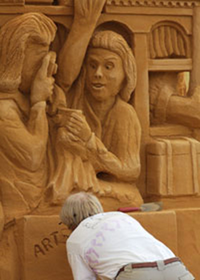 Sand Sculpture Of People Taking Pictures