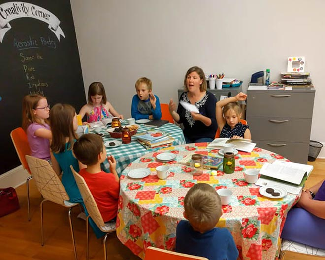 Woman talking to children while they have a snack