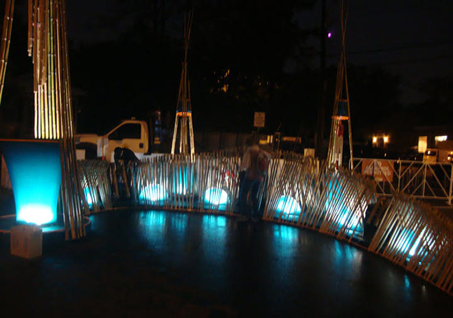 Legacy Works Sculpture with bamboo and blue lights at night