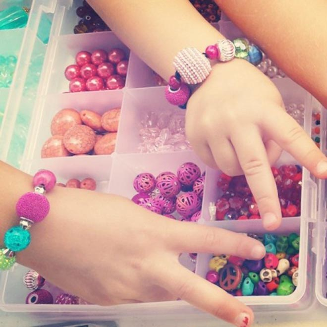 Children giving the peace sign over a tray of beads