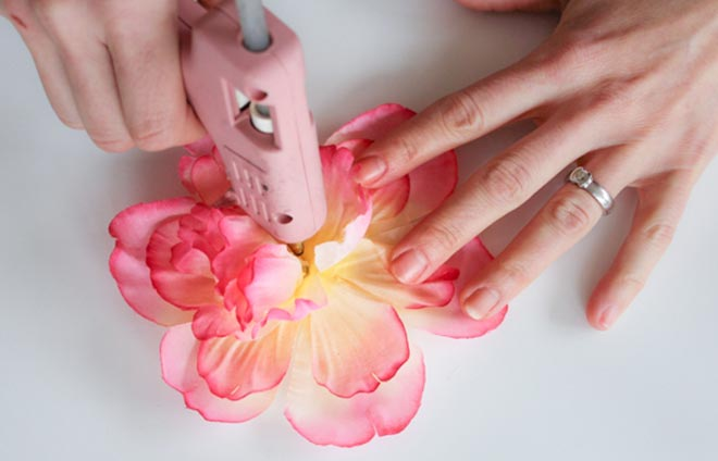 Person hot gluing a flower together