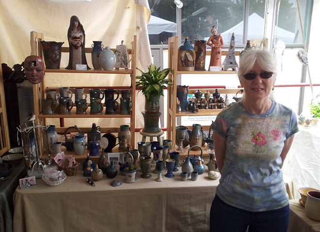 Woman in front of table with handmade pottery on it