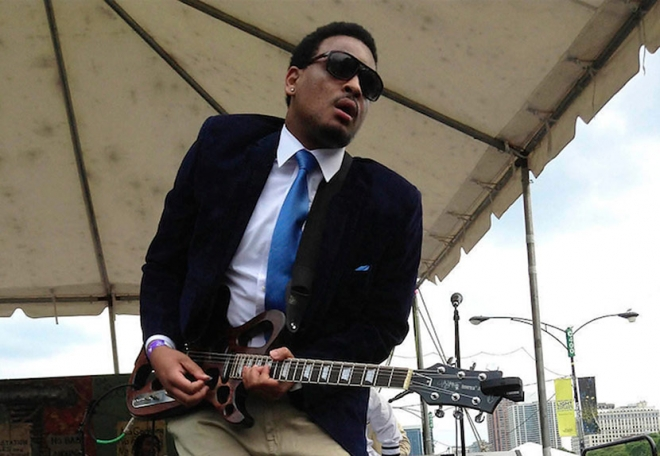 Jarekus Singleton playing guitar on outdoor stage