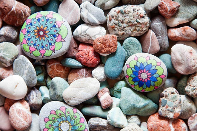 Detailed, ornate drawings on the rocks. Pebble painting. Colored stones.