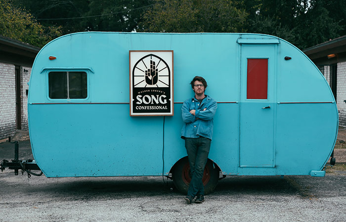 Walker Lukens Of Song Confessional Standing In Front Of A Blue Camper