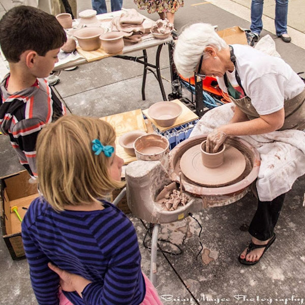 Member of the Triangle Potters Guild making pottery as children watch