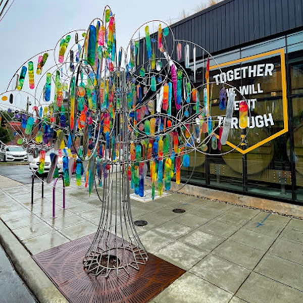 Metal wireframe tree with colored ribbons tied to it